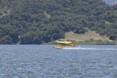 Yellow amphibious seaplane taking off from Lake Casitas, Ojai, California Stock Images