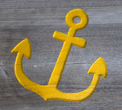 Yellow anchor carved in wood Stock Photos