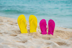 Free Yellow And Pink Sandals Stand In The Sand Against The Background Of The Sea. Royalty Free Stock Image - 97561126