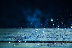 Yellow And Purple Glitter Lights Background. Vintage Sparkle Bokeh With Selective Focus. Defocused. On Wood Texture. Cool Blue Royalty Free Stock Image