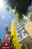 Apartment block sales sign. A block of new yellow apartments, shot vertically showing the Sales centre flag. Sydeny Australia. Copyspace Stock Photos