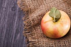 Yellow apple on burlap Stock Photo