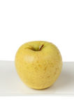 Yellow Apple Closeup on White Plate Stock Image