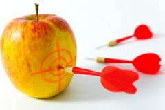Yellow apple with darts Royalty Free Stock Photography