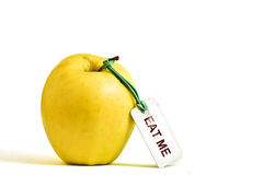 Yellow apple with EAT ME tag. Yellow apple with 'EAT ME' tag isolated on white background Stock Image