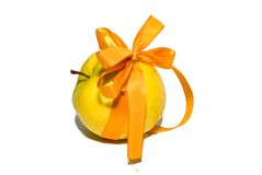 Yellow apple with a gift bow. On a white background Royalty Free Stock Photo