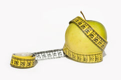 Yellow apple and measurement tape. Yellow apple surrounded by measurement tape Royalty Free Stock Images