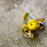 Yellow apple with measuring tape on concrete background. Top view.  Royalty Free Stock Images