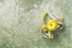 Yellow apple with measuring tape on concrete background. Top view.  Royalty Free Stock Image