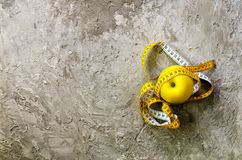 Yellow apple with measuring tape on concrete background. Top view.  Stock Photo
