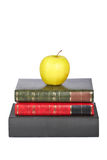Yellow apple on old books. Isolated on white background stock images