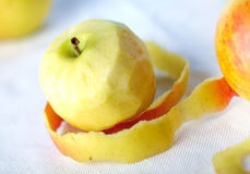 Yellow apple with peeled twisted skin Royalty Free Stock Photos