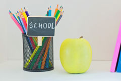 Yellow apple, pencils in case and multi colored books Stock Images