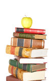Yellow apple on pile of books. Isolated on white background royalty free stock images