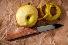 Yellow apple reinetas semi peeled with knife. royalty free stock photography