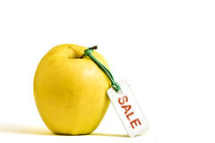 Yellow apple with SALE tag. Isolated on white background Stock Photos