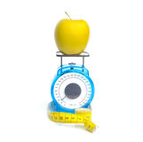 Yellow apple on scale Stock Images