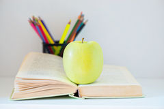 A yellow apple sitting on opened book Stock Image