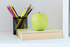 A yellow apple sitting on top of book Stock Photo