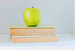 A yellow apple sitting on top of a stack of books Stock Photos