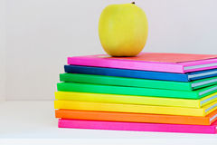 A yellow apple sitting on top of a stack of school books Stock Image
