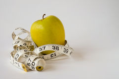 Yellow apple and tape measure on white background Stock Image