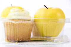 Yellow apple vs yellow cupcake Royalty Free Stock Images