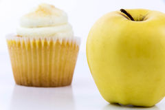 Yellow apple vs yellow cupcake Stock Image
