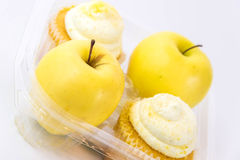 Yellow apple vs yellow cupcake Royalty Free Stock Photography