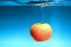 Yellow apple in the water splash over blue Stock Images