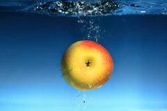 Yellow apple in the water splash over blue Royalty Free Stock Images