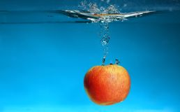 Yellow apple in the water splash over blue Stock Photo