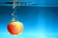 Yellow apple in the water splash over blue Royalty Free Stock Photos