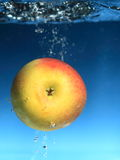Yellow apple in the water splash over blue Stock Image