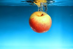 Yellow apple in the water splash over blue Stock Photography