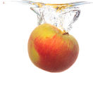 Yellow apple in the water splash over white Royalty Free Stock Photos