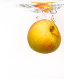 Yellow apple in the water splash over white Royalty Free Stock Photo