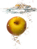 Yellow apple in the water splash over white Stock Images