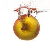 Yellow apple in the water splash over white Royalty Free Stock Photography