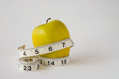 Yellow apple on white background with measuring tape. Fresh healthy yellow apple with measuring tape on white background stock photos