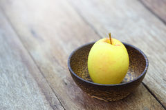 Yellow apple in wood bowl Stock Photos