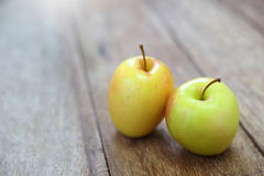 Yellow apple on wood Royalty Free Stock Image