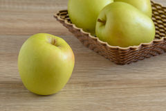 Yellow apples in a basket on the table. Horizontal Royalty Free Stock Photos