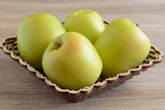 Yellow apples in a basket on the table. Horizontal Stock Images