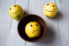 Yellow apples with drawn emotions. On wooden background royalty free stock image