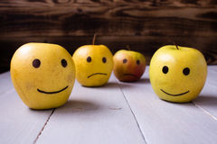 Yellow apples with drawn emotions. On wooden background royalty free stock images