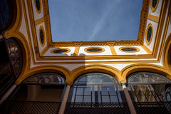 Yellow arch of a balcony against a blue sky in Seville, Spain, E. Urope on a summer day Royalty Free Stock Photos