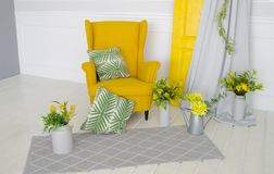 Yellow armchair in the interior with elements of home textiles, pillows and floral decor stock photography
