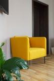 Yellow armchair near white wall Stock Photos