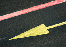 Yellow arrow. On a road Stock Images